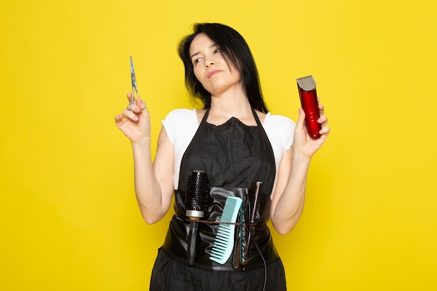 A front view beautiful female hairdresser in white t-shirt black cape with brushes with washed hair holding scissors and machine posing on the yellow background stylist barber hair