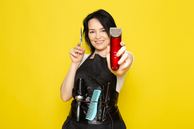 A front view beautiful female hairdresser in white t-shirt black cape with brushes with washed hair holding scissors and machine smiling on the yellow background stylist barber hair