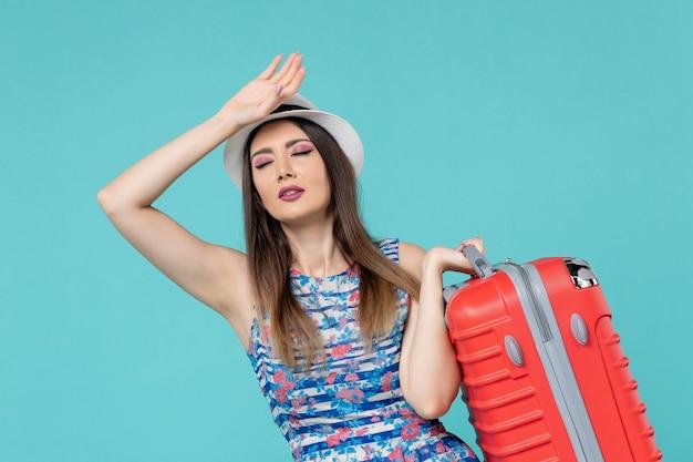 正面図美しい女性のバッグを保持し、青いスペースでの旅行の準備をしています