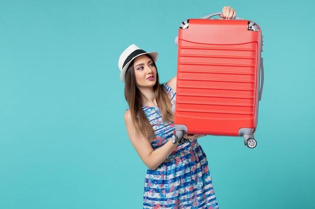 Bella borsa femminile della tenuta di vista frontale e preparazione per il viaggio sulla scrivania blu