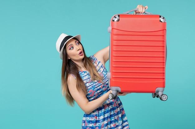Vista frontale bella borsa della holding femminile e preparazione per il viaggio su uno spazio azzurro