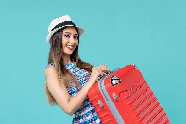 Bella borsa femminile della tenuta di vista frontale e preparazione per il viaggio che sorride sullo spazio blu