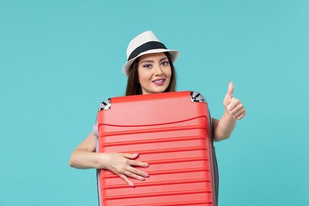 Vista frontale bella femmina che tiene borsa rossa e si prepara per il viaggio nello spazio blu
