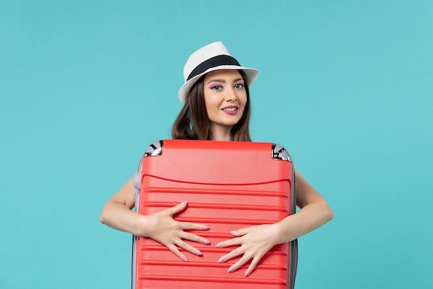 Vista frontale bella femmina che tiene borsa rossa e si prepara per il viaggio su uno spazio azzurro
