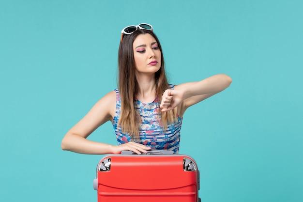 休暇の準備と青いスペースで時間をチェックする正面図美しい女性