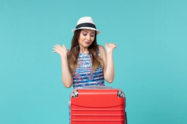 파란색 바닥 항해 여행 여행 바다 휴가 여자에 그녀의 빨간 가방과 함께 휴가를 준비하는 전면보기 아름다운 여성