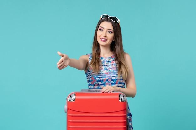 青いスペースで誰かに挨拶する赤いバッグで休暇の準備をしている正面図美しい女性