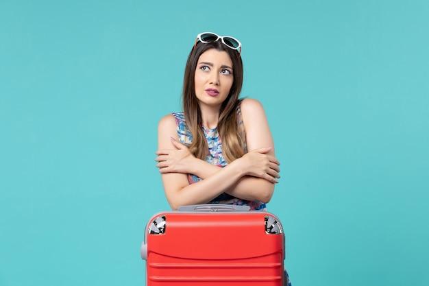 Вид спереди красивая женщина готовится к отпуску с красной сумкой, дрожащей на синем пространстве