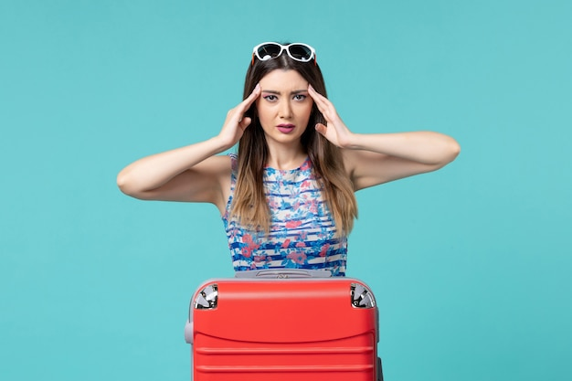 Front view beautiful female preparing for trip having headache on blue space