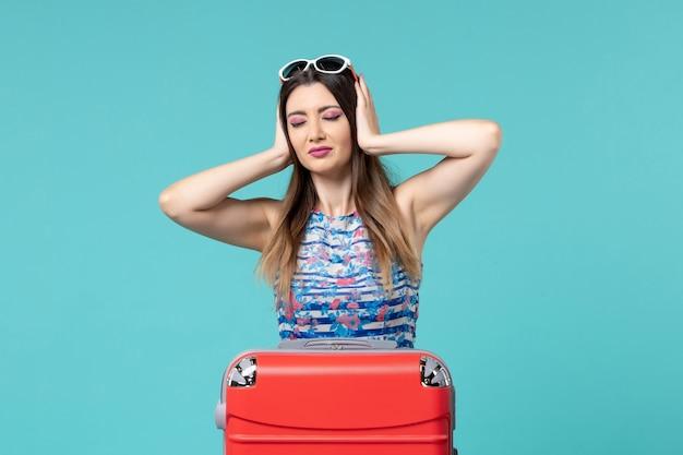Bella femmina di vista frontale che prepara per il viaggio che ha mal di testa sullo spazio blu