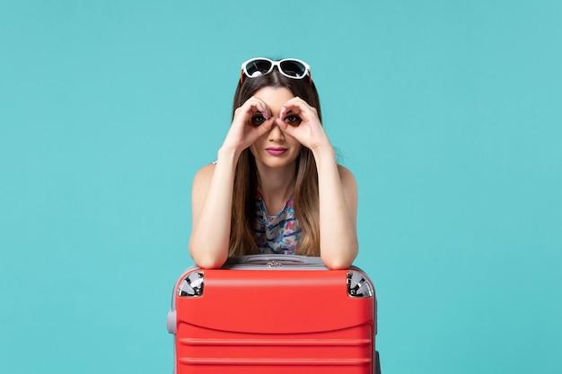 Bella femmina di vista frontale che prepara per il viaggio con la sua grande borsa rossa sulla ragazza di viaggio di viaggio di viaggio di vacanza di mare del pavimento blu