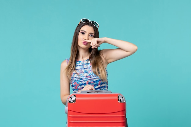 Bella femmina di vista frontale che prepara per il viaggio con la sua grande borsa rossa sullo spazio blu-chiaro