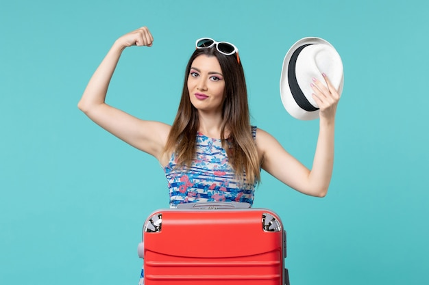 Bella femmina di vista frontale che prepara per la vacanza con la borsa ed il cappello che flettono sullo spazio blu