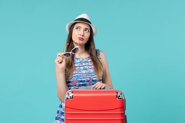 Bella femmina di vista frontale che prepara per la vacanza con la sua borsa rossa sullo scrittorio blu