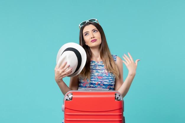 Bella femmina di vista frontale che prepara per la vacanza con la borsa rossa sullo scrittorio blu