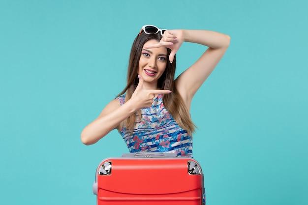Bella femmina di vista frontale che prepara per la vacanza con la borsa rossa sullo spazio blu