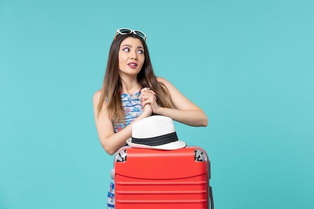 Bella femmina di vista frontale che prepara per la vacanza con la borsa ed il cappello rossi sullo spazio blu-chiaro