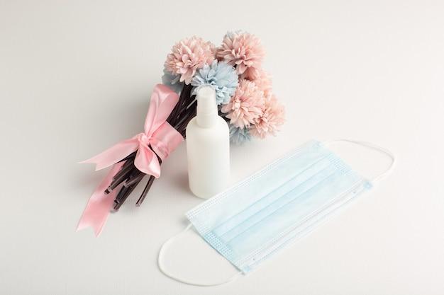 Vista frontale bellissimi fiori con spray e maschera sulla superficie bianca