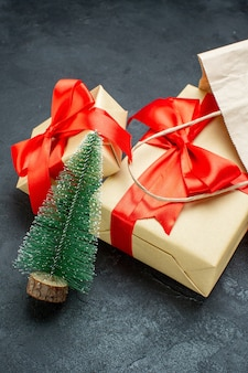 Front view of beautiful gifts with red ribbon and christmas tree on a dark table