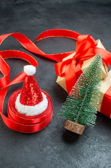 Front view of beautiful gifts with red ribbon and christmas tree santa claus hat on a dark table