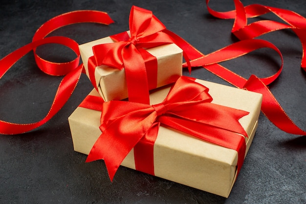 Front view of beautiful gifts with red ribbon on dark background