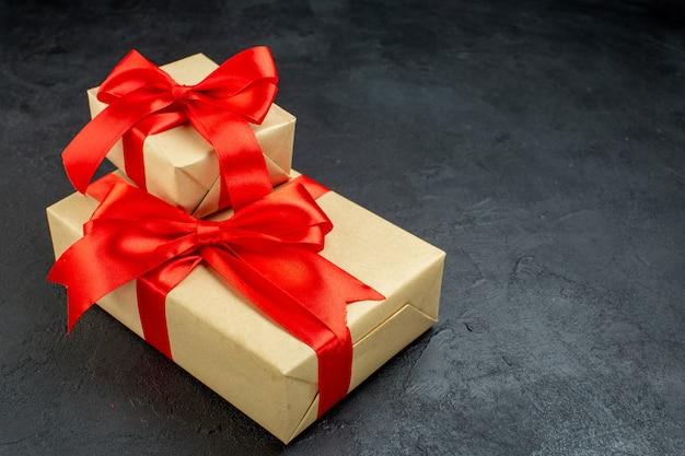 Vista frontale di bellissimi doni con nastro rosso sul lato destro su sfondo scuro