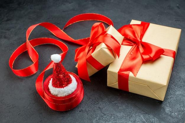 Vista frontale di bellissimi regali con nastro rosso e cappello di babbo natale su un tavolo scuro