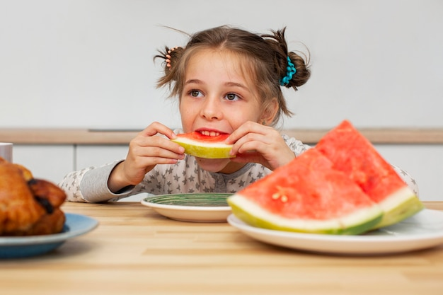 Front view of beautiful girl eating watermelon