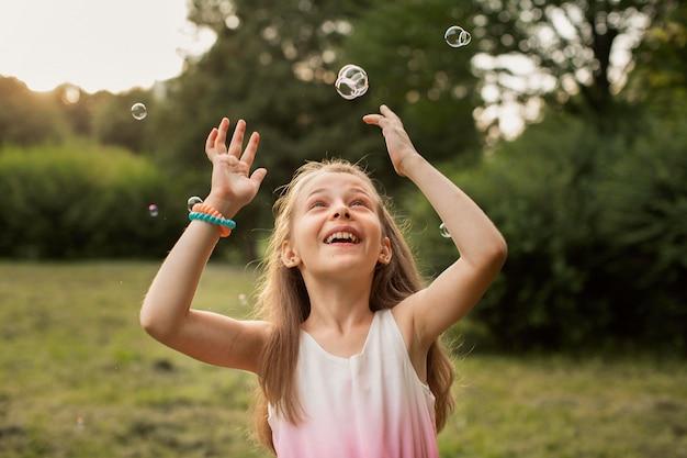 Vista frontale della bella ragazza felice con bolle di sapone