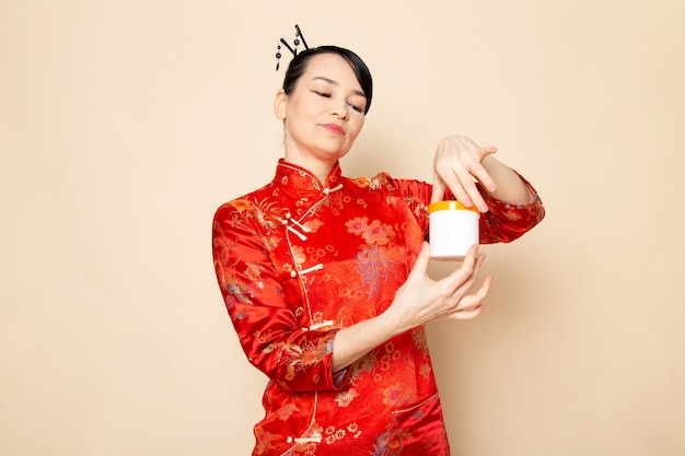 A front view beautiful japanese geisha in traditional red japanese dress with hair sticks posing holding cream can smiling on the cream background ceremony japan