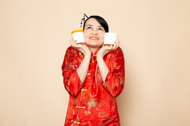 A front view beautiful japanese geisha in traditional red japanese dress with hair sticks posing holding cream cans smiling on the cream background ceremony japan