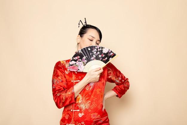 Una bella geisha giapponese di vista frontale in vestito giapponese rosso tradizionale con i bastoncini di capelli che posano tenendo il ventaglio pieghevole elegante sulla cerimonia crema giapponese del fondo