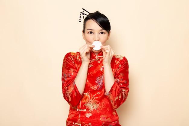 Una bella geisha giapponese di vista frontale in vestito giapponese rosso tradizionale con i bastoncini di capelli che posano tenendo la piccola espressione bianca del cotone sulla cerimonia crema giappone del fondo