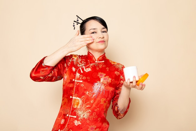 A front view beautiful japanese geisha in traditional red japanese dress with hair sticks posing using cream can smelling on the cream background ceremony japan