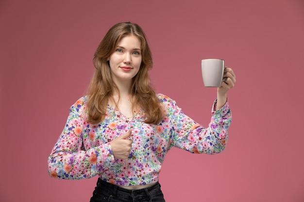 Вид спереди красивая дама показывает палец вверх и ее чашку