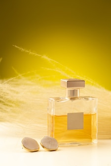 Front view of beautiful light perfume inside flask on the yellow surface