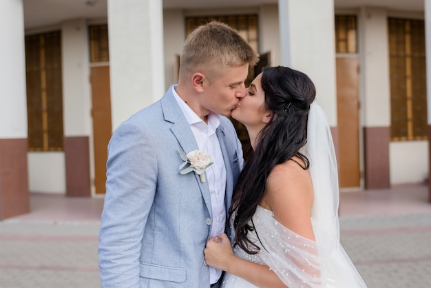 Front view of beautiful newlyweds hugging and kissing on the street on a summer day