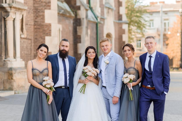 Front view of beautiful newlyweds with friends looking at the camera and smiling on the street
