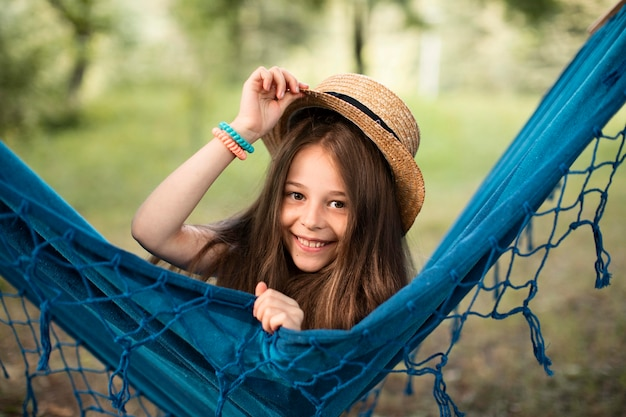 Front view of beautiful smiling girl in hammock