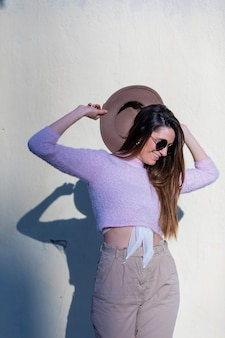 Front view of beautiful trendy young woman wearing sunglasses and hat standing in the street while posing in a sunny day