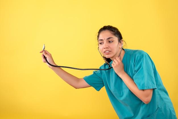Vista frontale bella donna medico in uniforme utilizzando lo stetoscopio in piedi su sfondo giallo