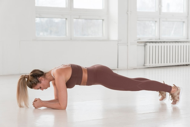 Front view of beautiful woman doing plank