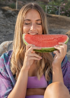 Front view of beautiful woman eating watermelon