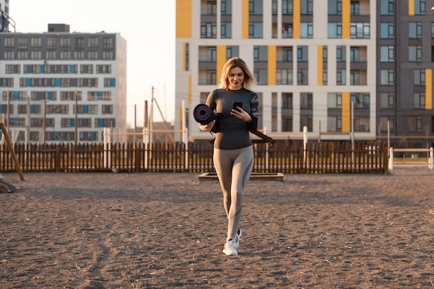 Front view of a beautiful woman in gray sportswear, looking at the phone, holding a yoga mat with her other hand. woman walks to the playground for doing sports at sunset.