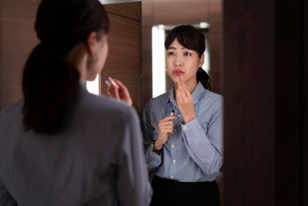Vista frontale di bella donna guardarsi allo specchio