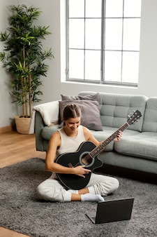 Front view of beautiful woman playing guitar