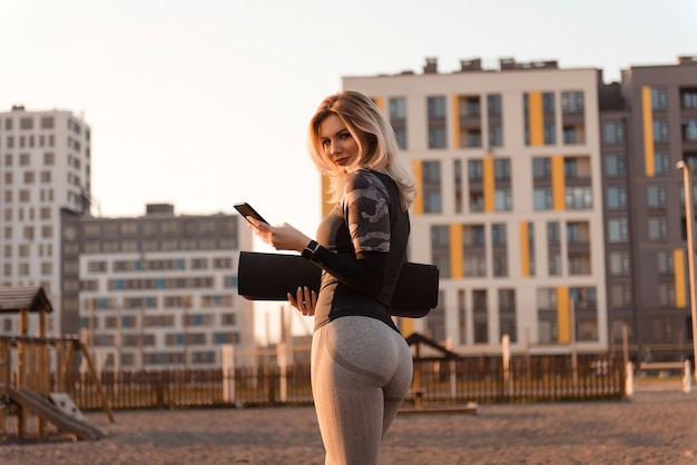 Front view of a beautiful woman in sexy gray sportswear, looking to the camera. woman holding phone and yoga mat. woman walks to the playground for doing sports at sunset.