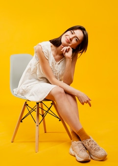 Front view of beautiful woman sitting on chair