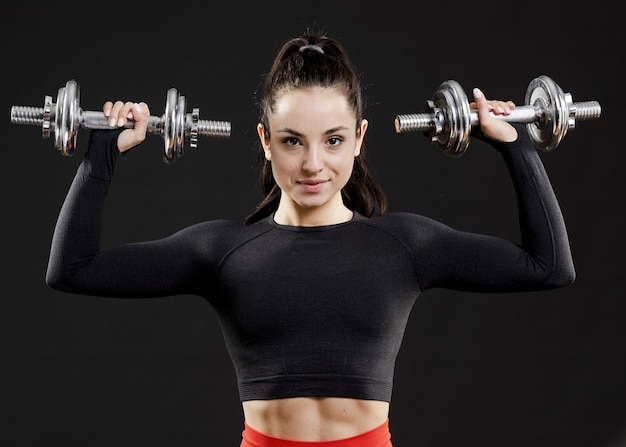 Front view of beautiful woman with dumbbells