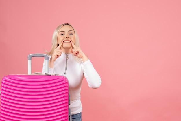 Vista frontale bella donna con la valigia rosa che punta il suo sorriso